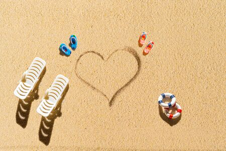 Aerial view of two pair of flip flops, sunbed, lifebuoy in shape of heart on sandy tropical beach. Valentines day. Holiday concept. Creative, background, travel, summer. Flat lay