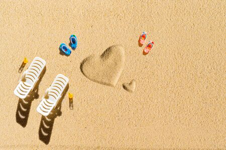 Aerial view of two pair of flip flops, sunbed in shape of heart on sandy tropical beach. Valentines day. Holiday concept. Creative, background, travel, summer. Flat lay