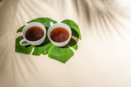 Cup coffee on sand of tropical beach under palm tree  branches shadow.