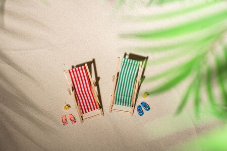 Aerial view two deck chair, glass of juice, flip flops on sand through the branches of palm and shadow palm tree. Travel, holiday, summertime, romantic concept. Top view. Stok Fotoğraf