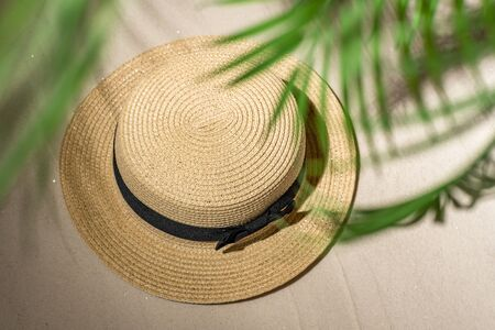 Summer straw hat on sand through the branches of palm and shadow palm tree. Travel, holiday, summertime concept. Top view. Stok Fotoğraf