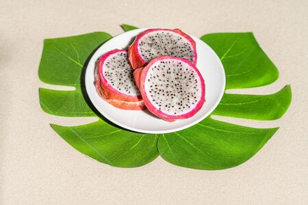 Dragon fruit, pitaya on palm tree leaves on the sand of tropical beach. Exotic food, snack. Summer travel Stok Fotoğraf