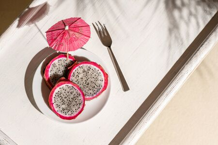 Dragon fruit, pitaya on a white wooden tray on the sand of tropical beach under a palm tree. Exotic food with umbrella topical toothpick, snack. Summer travel