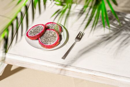 Dragon fruit, pitaya on a white wooden tray on the sand of tropical beach under a palm tree. Exotic food, snack. Summer travel
