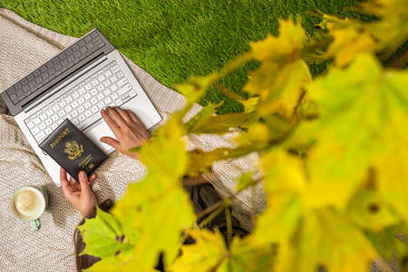 Autumn. Woman on the plaid with laptop and American passport, cup of coffee under tree, branch of maple leaves on the green grass in the park. Travel, booking concept. Top view Stok Fotoğraf