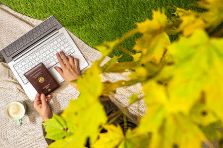 Autumn. Woman on the plaid with laptop and Germany passport, cup of coffee under tree, branch of maple leaves on the green grass in the park. Travel, booking concept. Top view