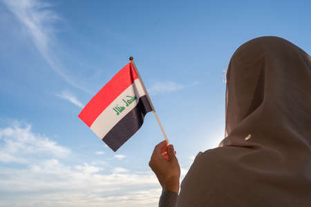 Silhouette of muslim woman in head scarf with Iraq flag at blue sunset sky. Concept of freedom
