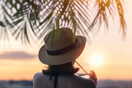 Back view of a beautiful girl with mineral water in a glass in a straw hat against the background of the sea in branches of palm trees. Sunset beach. Summer and freedom concept.