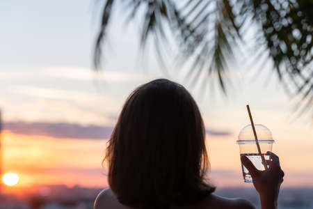 Back view of a beautiful girl with mineral water in a glass against the background of the sea in branches of palm trees. Sunset beach. Summer and freedom concept.