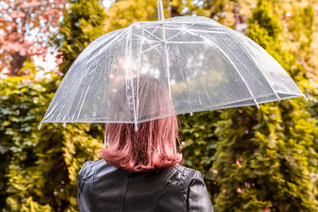 Autumn. Lonely redhead girl under a transparent umbrella with rain drops walking in a park, garden. Rainy day landscape