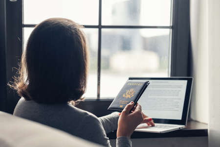 Woman holding passport filling visa application form on the laptop. Online and home work concept. Standard-Bild