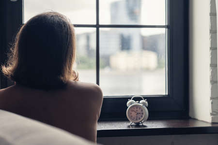 Back view of lonely caucasian young woman with alarm clock sitting near window at cold winter day.