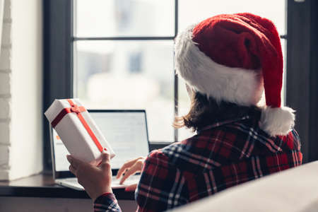 Woman in a red santa claus hat using laptop for making order sitting near window. Christmas online gifts shopping. Concept