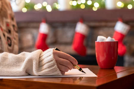 Woman writing letter to santa claus using fountain pen on sheet of paper at christmas fireplace with decoration of light bulbs drinking hot cocoa and marshmallow. Foto de archivo