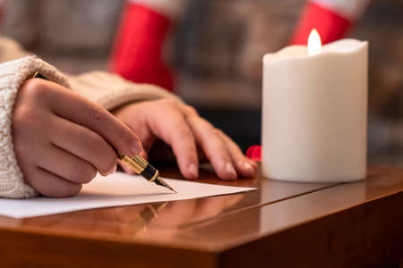 Woman writing wish list using fountain pen on sheet of paper at christmas fireplace with decoration of light bulbs and candle on table.