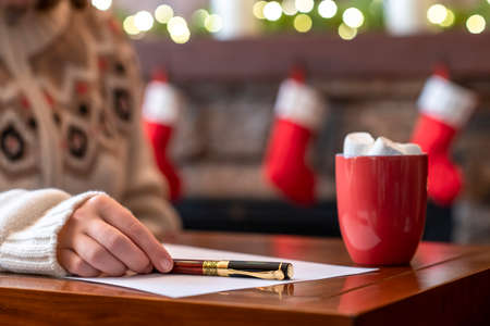 Woman writing wish list using fountain pen on sheet of paper at christmas fireplace with decoration of light bulbs drinking hot chocolate and marshmallow.