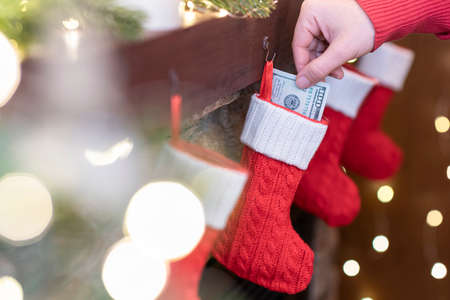 Woman putting american dollars in сhristmas red socks for gifts on the fireplace in bokeh lights.