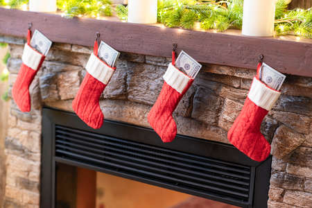 American, US dollars in сhristmas red socks for gifts on the fireplace in bokeh lights.