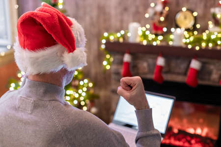 Back view of angry man freelancer in santa claus hat, raising and swinging fist on laptop screen sitting near christmas tree and fireplace. Concept