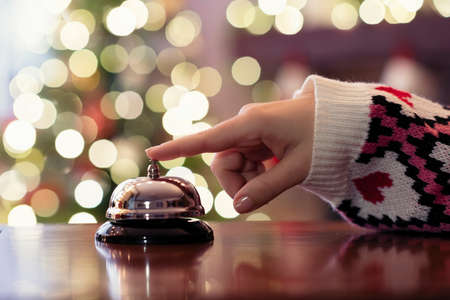 Christmas travel. Hand of guest ringing bell on reception desk of guesthouse and color shining garland on christmas tree on background. Hotel, restaurant. Banque d'images