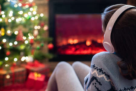 Woman in headphones sitting and warming at winter evening near fireplace flame and christmas tree. 写真素材