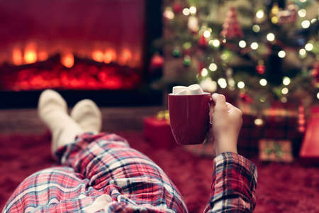 Woman in pajamas with cup of hot cocoa and marshmallow lying and warming at winter evening near fireplace flame and christmas tree.