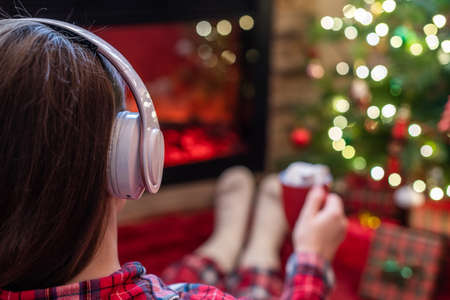 Woman in pajama in headphones with cup of hot cocoa and marshmallow sitting and warming at winter evening near fireplace flame and christmas tree.