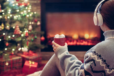 Woman in headphones with cup of hot cocoa and marshmallow sitting and warming at winter evening near fireplace flame and christmas tree.