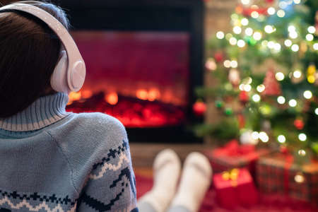 Alone sad woman in headphones sitting and warming at winter evening near fireplace flame and christmas tree. 写真素材