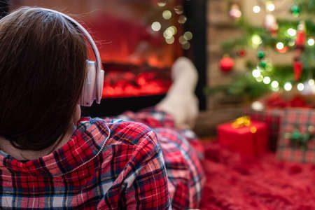 Woman in pajama in headphones lying listening music and warming at winter evening near fireplace flame christmas tree. 写真素材