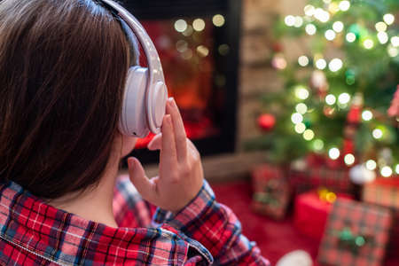 Woman in pajama in headphones sitting and warming at winter evening near fireplace flame and christmas tree. 写真素材