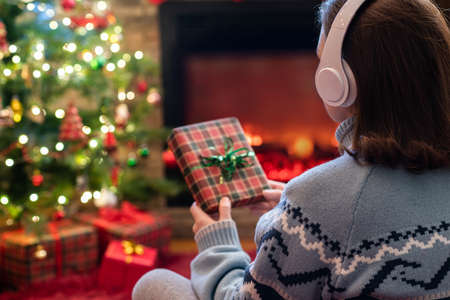Woman in headphones with christmas gift box in hand sitting on fluffy plaid near fireplace and christmas tree. 写真素材