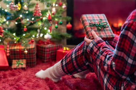 Woman in pajamas with christmas gift box in hand sitting on fluffy plaid near fireplace and christmas tree. 写真素材