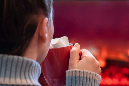 Woman with cup of hot cocoa and marshmallow sitting and warming at winter evening near fireplace flame.