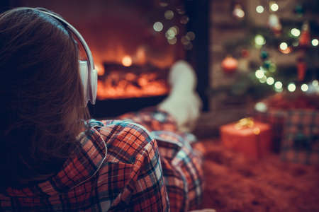 Woman in pajama in headphones lying, relaxing and warming at winter evening near fireplace flame christmas tree.