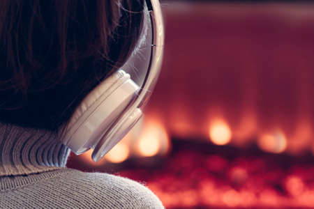 Woman in headphones sitting and warming at winter evening near fireplace flame.