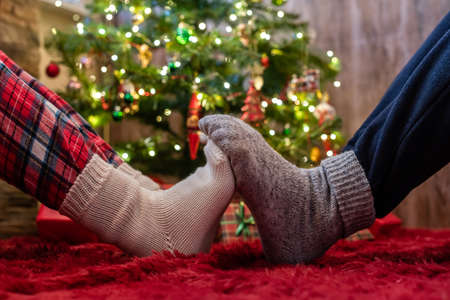 Male and female feet in winter socks touching each other. Man and woman sitting near a Christmas tree with gifts. Concept