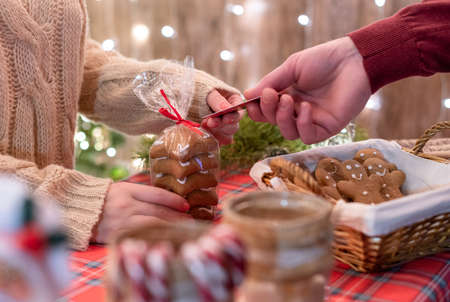 Man customer buying christmas sweets, gingerbread at the bakery giving credit card to the woman seller