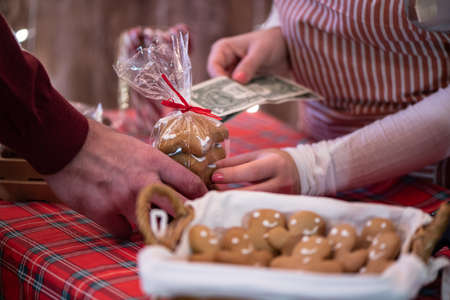 Man customer buying christmas sweets at the bakery giving dollars to the woman seller