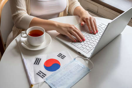 Woman tourist having breakfast with cup of coffee working on laptop. Flag of South Korea, medical protective face mask on table of cafe. Protection from bacteria and viruse in a public place. Concept.