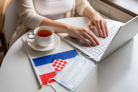 Woman tourist having breakfast with cup of coffee working on laptop. Flag of Croatia, medical protective face mask on table of cafe. Protection from bacteria and virus in a public place. Concept.