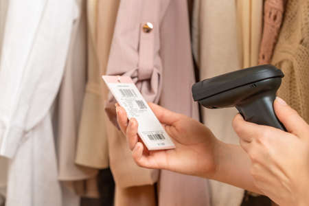 A warehouse woman employee accepts chinese clothes using barcode scanner reading a bar code from price tag of female blazer