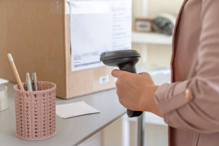Woman employee of post office scanning parcel using barcode scanner to confirm sending customer. Home delivery service.