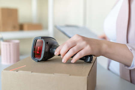Woman employee of post office scanning parcel using barcode scanner to confirm sending customer. Home delivery service. Stock Photo