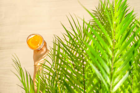 Woman hand under palm tree branches with glass of water with slice orange. Female relaxation on the sand of the beach at summer vacation. Top view