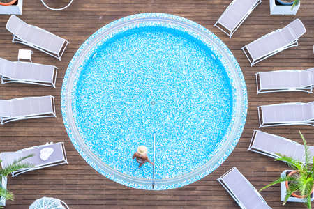 Young alone beautiful sports woman in bikini and hat is swimming on wooden terrace. Aerial drone view from above. Tropical summer luxury hotel