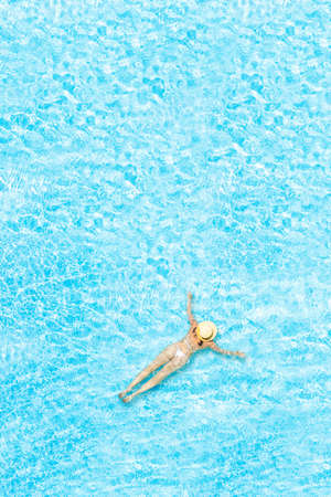 Top view of young woman in bikini and straw hat is swimming in transparent blue sea, lagoon. Aerial, drone view. Vertical ratio