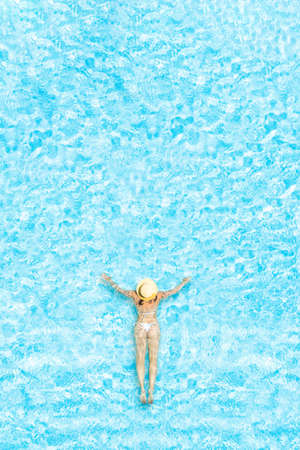 Young alone beautiful sports woman in bikini and hat is swimming in swimming pool. Aerial drone view from above. Vertical ratio, size