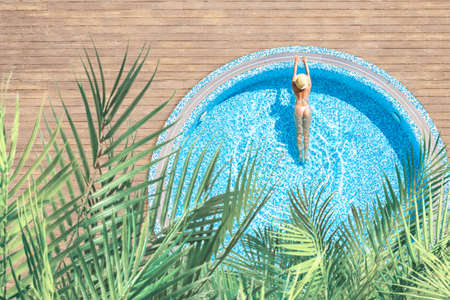 Young alone, beautiful sports woman in bikini and hat is swimming in swimming pool with palm trees. Aerial, above, drone view. Tropical summer luxury hotel
