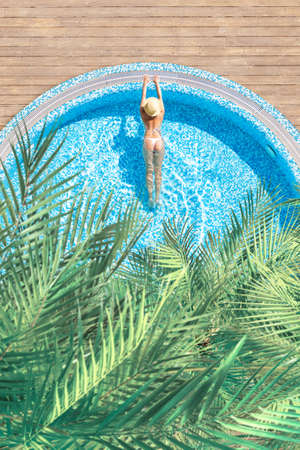 Young alone, beautiful sports woman in bikini and hat is swimming in swimming pool with palm trees. Aerial, above, drone view. Vertical ratio, size 免版税图像